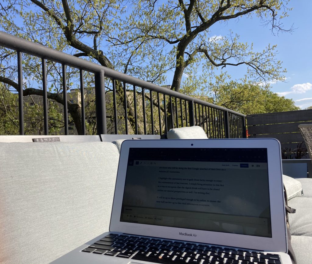 Photo of a laptop on a outdoor furniture with a background of trees and blue sky.